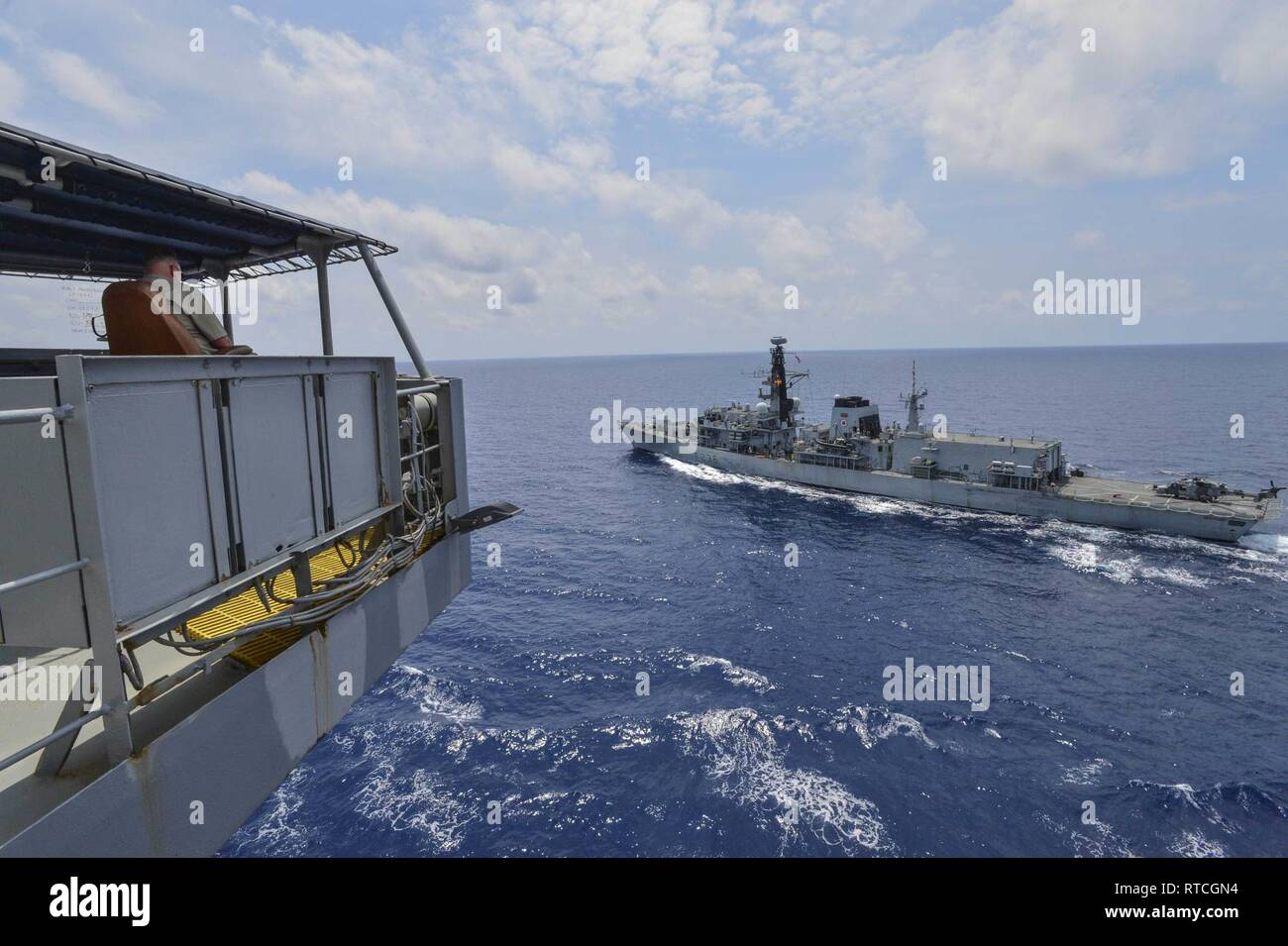 GULF OF THAILAND (Feb. 18 ,2019) Civilian Mariner Kevin Sauls, Ship's Master aboard the Henry J. Kaiser-class fleet replenishment oiler USNS Guadalupe (T-AO 200),  observes the Duke-class frigate HMS Montrose (F 236) during a replenishment-at-sea drill. Guadalupe is conducting operations, providing logistical support to U.S. Navy and allied forces operating in the U.S. 7th Fleet area of responsibility. Stock Photo