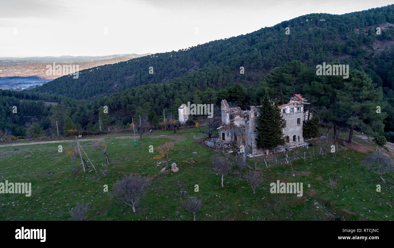 Aerial view demolished house in the middle of the Sierra de El Tiemblo surrounded by forest - Stock Image