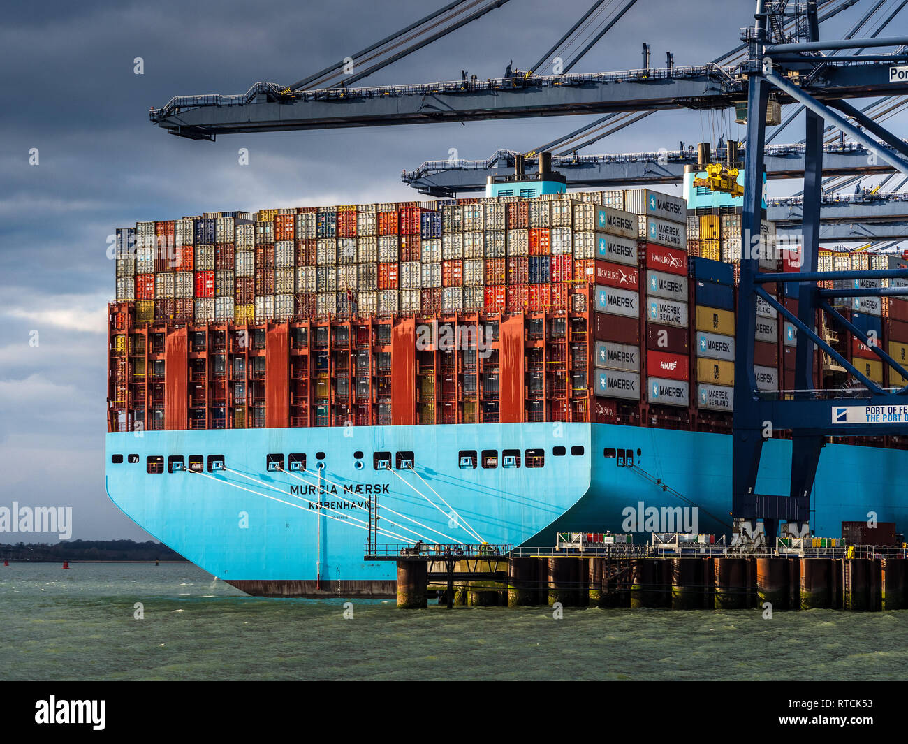 UK Foreign Trade - Shipping containers being loaded and unloaded from a Maersk ship in Felixstowe. UK's largest Container Port on the East coast Stock Photo
