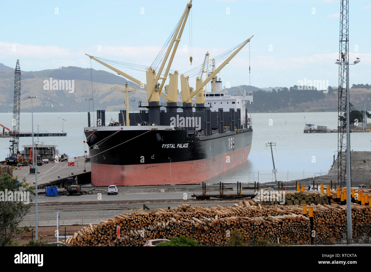 A cargo ship awaiting its load of timber at the Log Yard in Lyttleton Port of Christchurch New Zealand. - Stock Image
