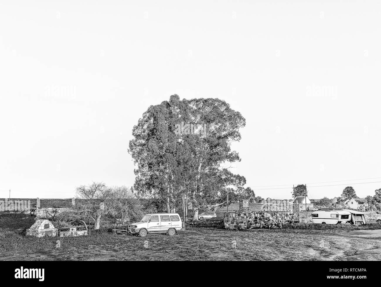 NIEUWOUDTSVILLE, SOUTH AFRICA, AUGUST 29, 2018: The camping area at Matjiesfontein farm in the Northern Cape Province. Vehicles, a caravan and an hist - Stock Image