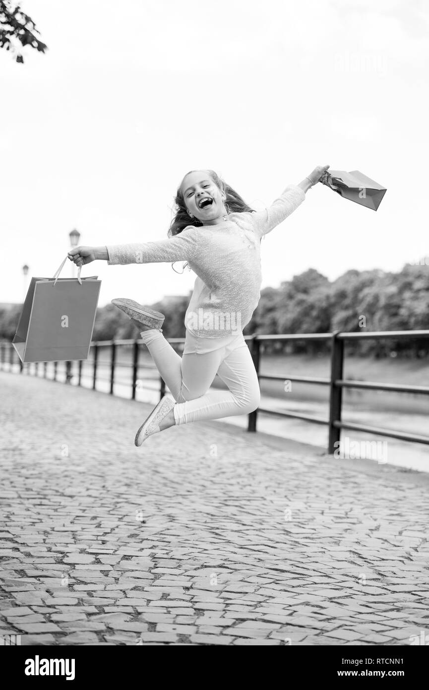 5503d093 Pretty little girl jumping on the street with the pink shopping bags -