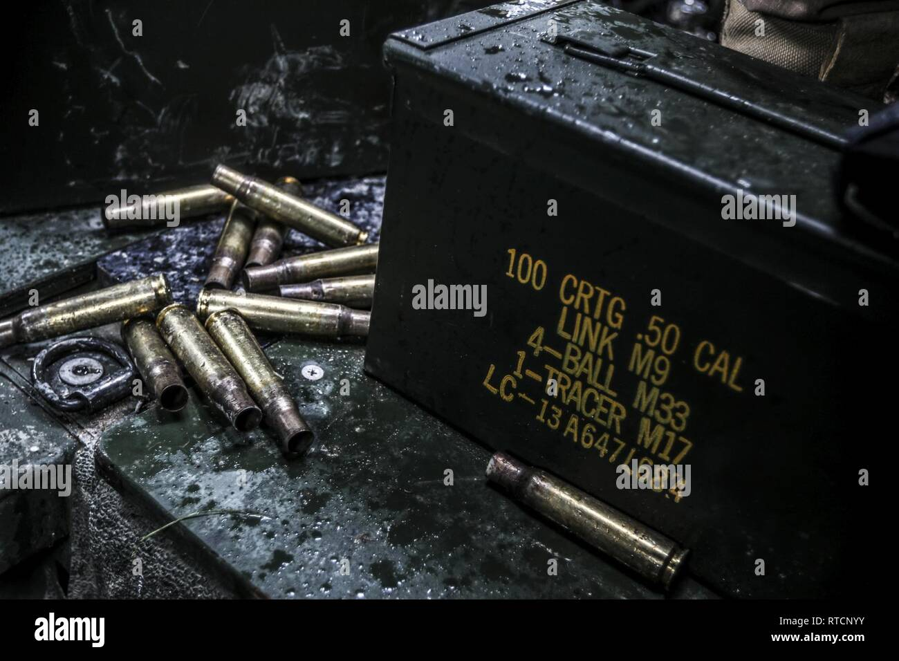 Expended ammo casings, from one crews's .50 cal prequalification run, get wet from winter downpours during Operation Cold Steel III at Fort Hunter Liggett, Calif., Feb. 14, 2019. Operation Cold Steel III trains and qualifies Army Reserve Soldiers on M2 .50 caliber machine guns, M19 40 mm automatic grenade launchers and M240 7.62 mm machine guns weapons systems in ground and mounted military vehicles, in order to provide lethal and combat ready units ready to deploy anywhere in the world. - Stock Image