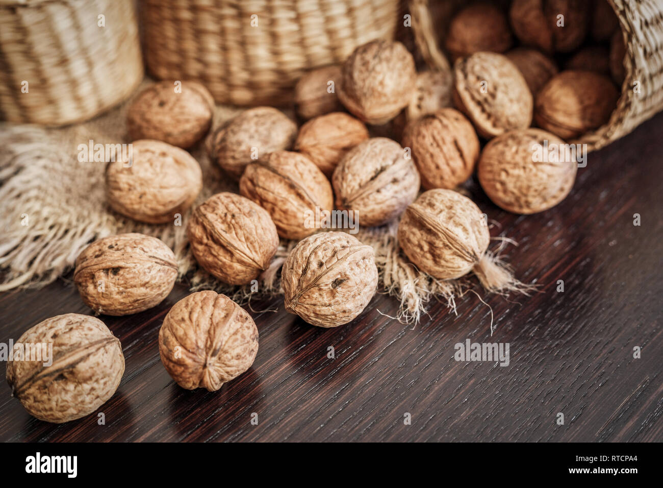 Close-up view of whole walnuts scattered on a dark wooden table with rustic background, selective focus. Healthy food concept. Stock Photo