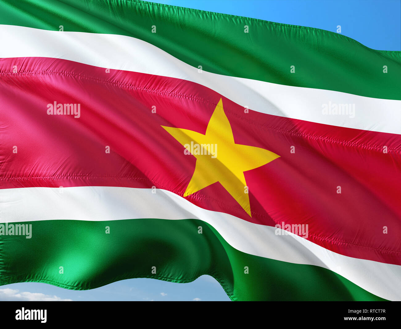 Flag of Suriname waving in the wind against deep blue sky. High quality fabric. - Stock Image