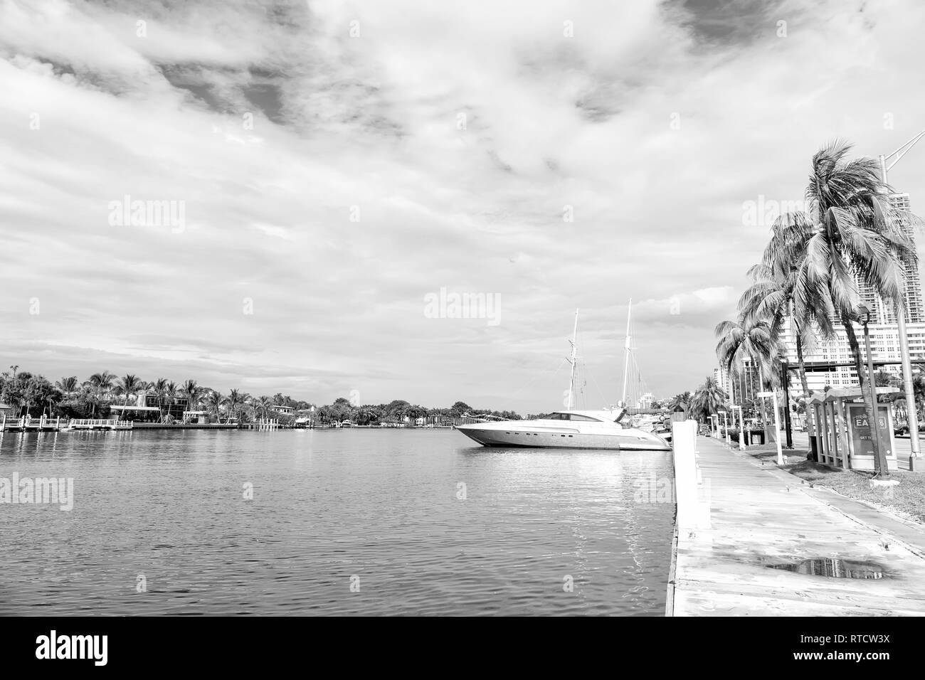 Miami beach or south beach. yachts and luxury sail boats parked at blue sea dock or bay pier green palm trees and buildings on sunny day on cloudy sky background. Summer vacation and travelling - Stock Image