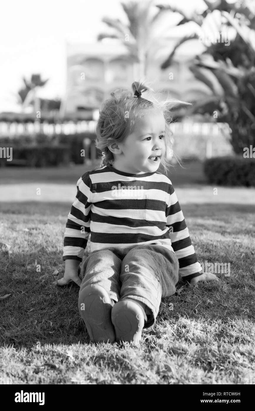 small baby boy or cute child with happy face and blonde hair in stripped shirt sitting on green grass barefoot sunny outdoor on natural background - Stock Image