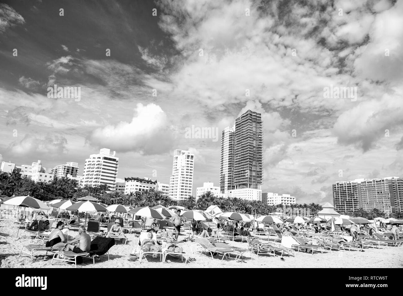Miami, USA - January 10, 2016: Miami beach or south beach. people sunbathing on deck chairs under blue umbrellas on beach with high buildings on cloudy blue sky. Summer vacation. Lounge and leisure - Stock Image