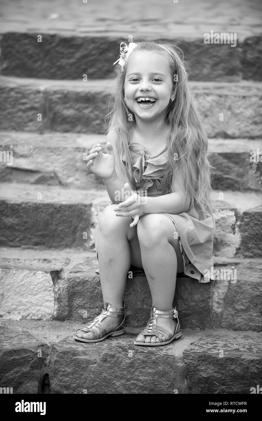 small happy baby girl or cute child with adorable smiling face and bow in blonde hair in blue dress outdoor sitting on colorful stony stairs background - Stock Image