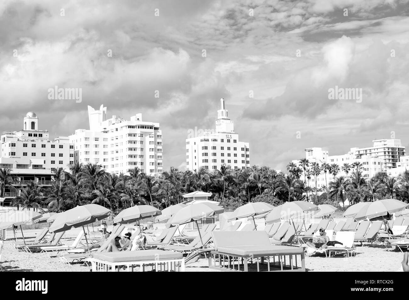 Miami, USA - January 10, 2016: South beach or miami beach. people relaxing on deck chairs under blue umbrellas on sunny sandy beach with palms, high buildings on cloudy blue sky. Summer vacation. - Stock Image