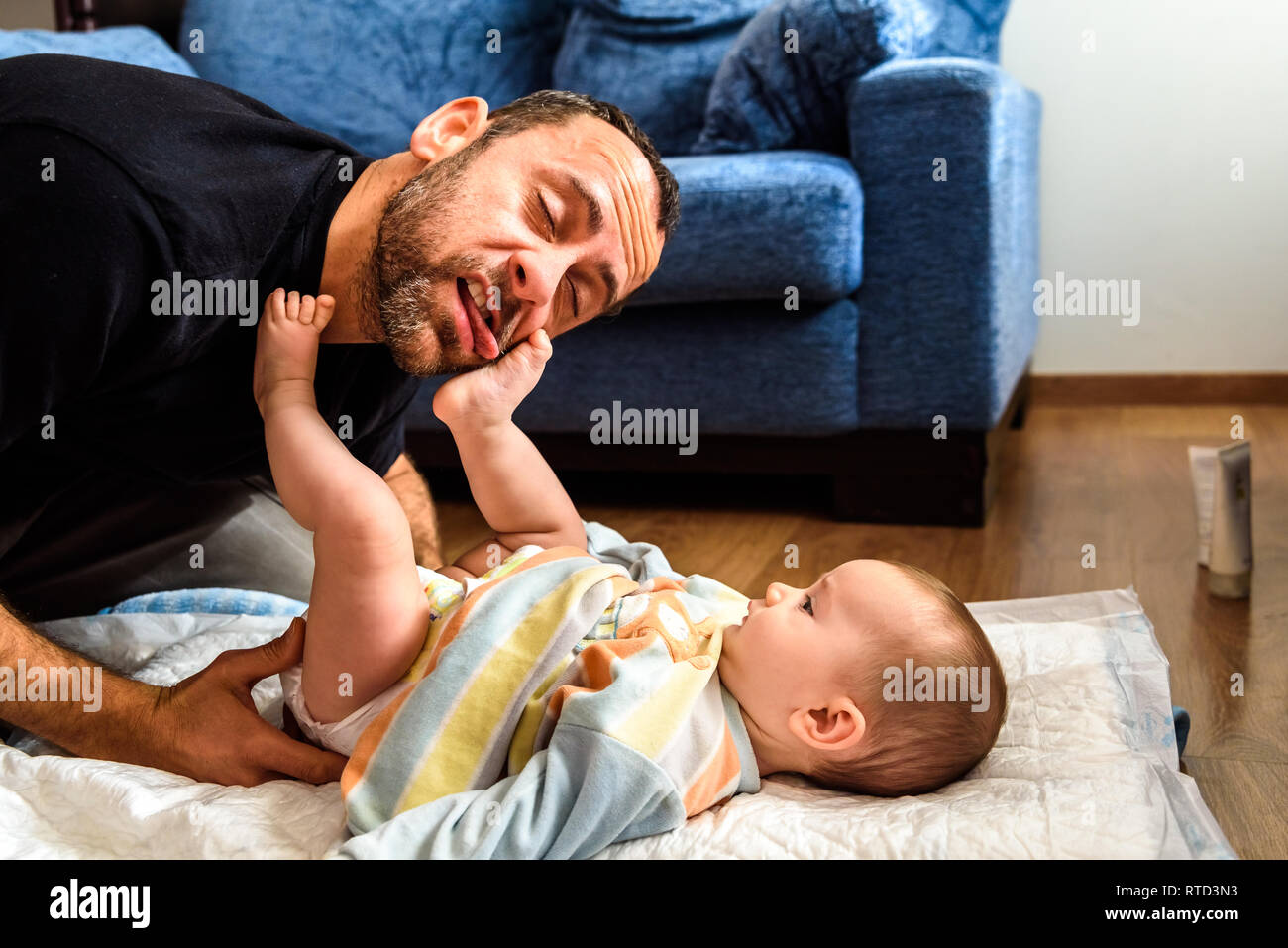 Dad struggling with his baby daughter to change dirty diapers putting faces of effort, concept of fatherhood. - Stock Image