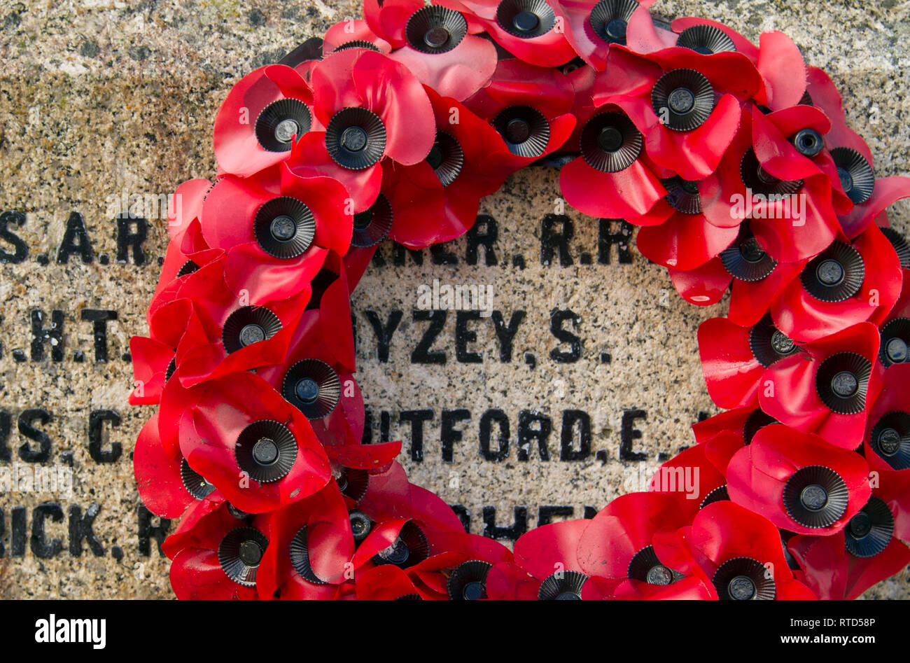 Rememberence poppy wreath on a war memorial in Lydford, Devonshire, UK - Stock Image