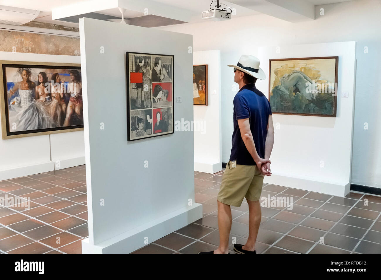 Cartagena Colombia Old Walled City Center centre Centro Museo de Arte Moderno modern art museum gallery exhibit inside paintings sculpture man looking - Stock Image