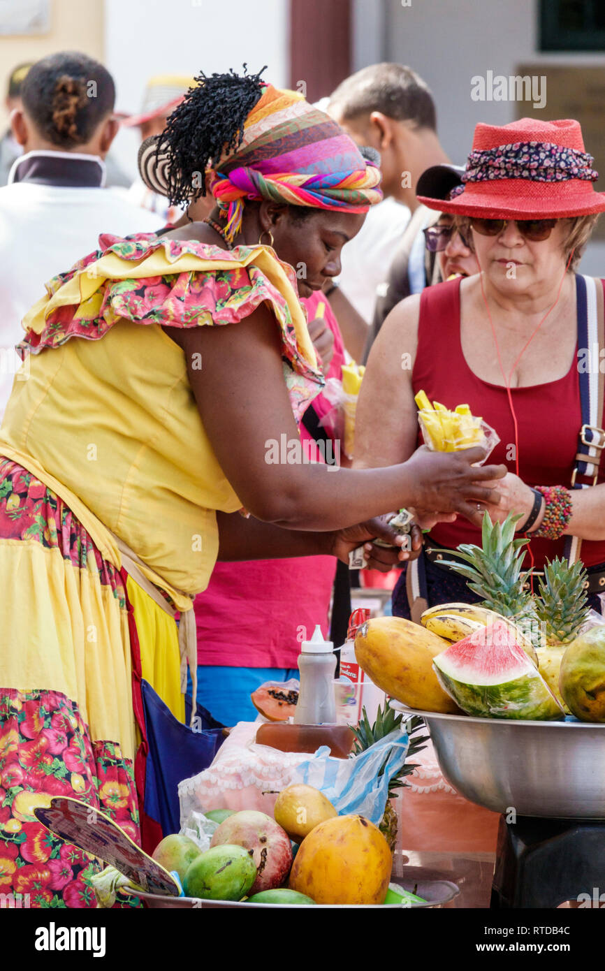 Cartagena Colombia Old Walled City Center centre Centro Plaza San Pedro Claver Black Afro Caribbean Palenqueras woman fruit vendor traditional costume - Stock Image