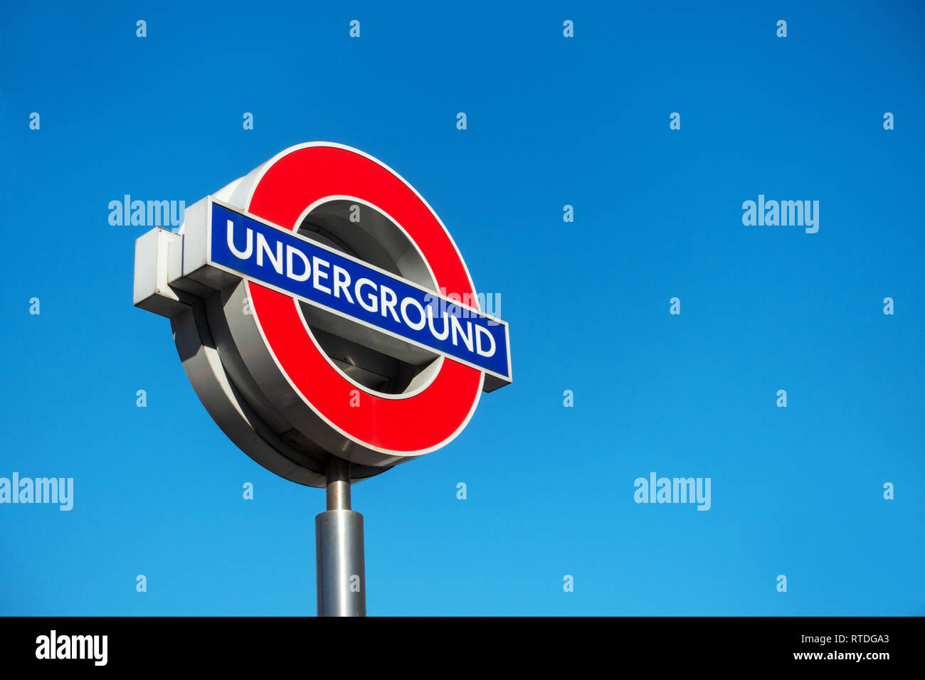 Close up of a contemporary tube sign for the London Underground transportation systems in London against a blue sunny sky - Stock Image