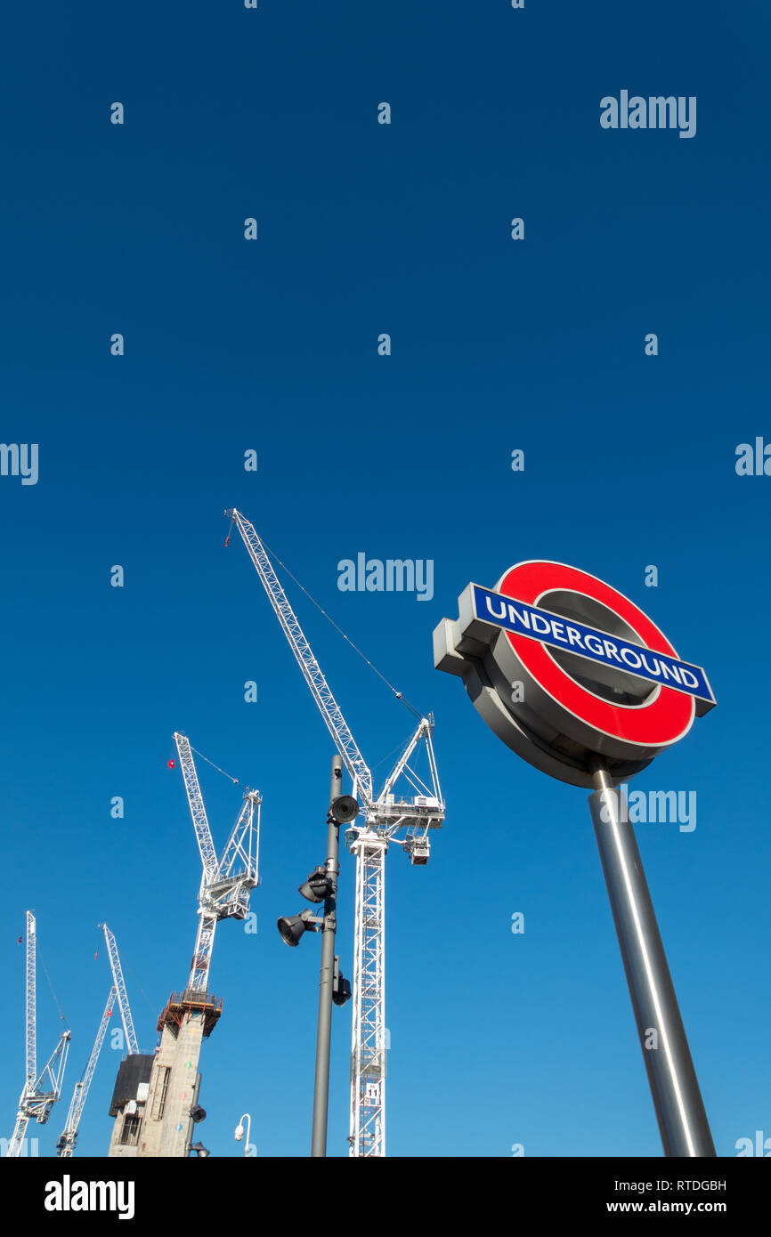 Close up of a contemporary traditional tube sign for the London Underground transportation systems in London against a blue sunny sky with white const - Stock Image
