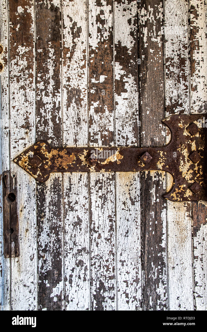 Detailed close-up of rusty old hinge on a door with peeling paint - Stock Image