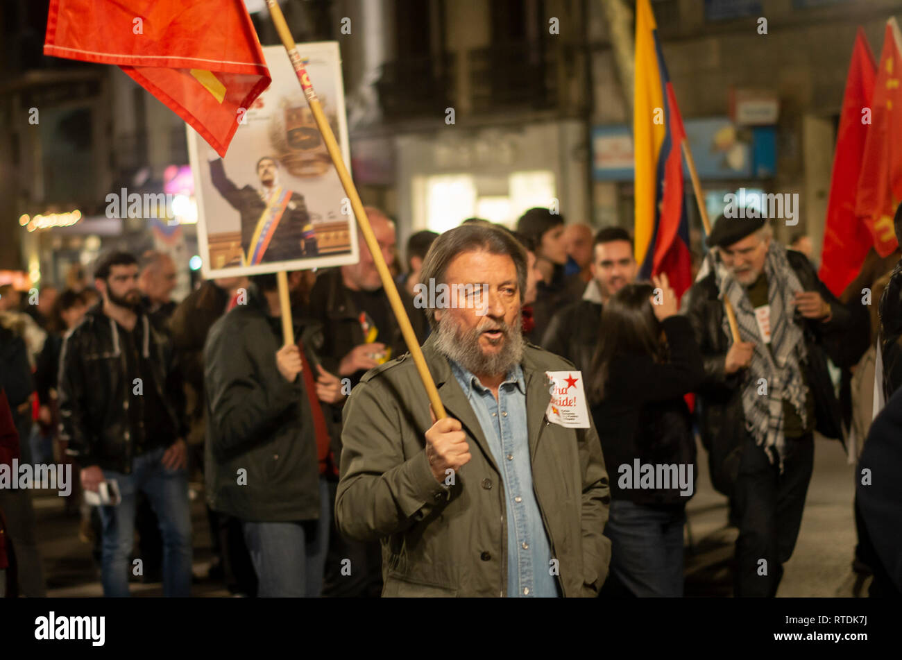 Protesters are seen holding flags during the protest. Hundreds of people protest against the intervention of United States in Venezuela marching from Atocha to Puerta del Sol in Madrid. Stock Photo