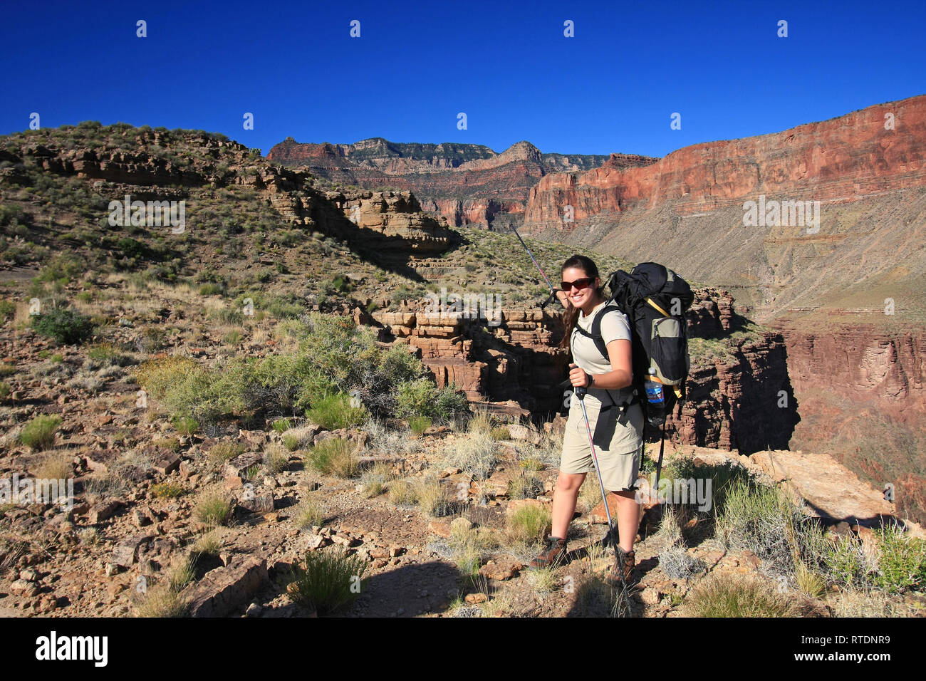 Young woman backpacker on the Tonto Trail pointing to trailhead where her hike started on the Grandview Trail in Grand Canyon National Park, Arizona. - Stock Image