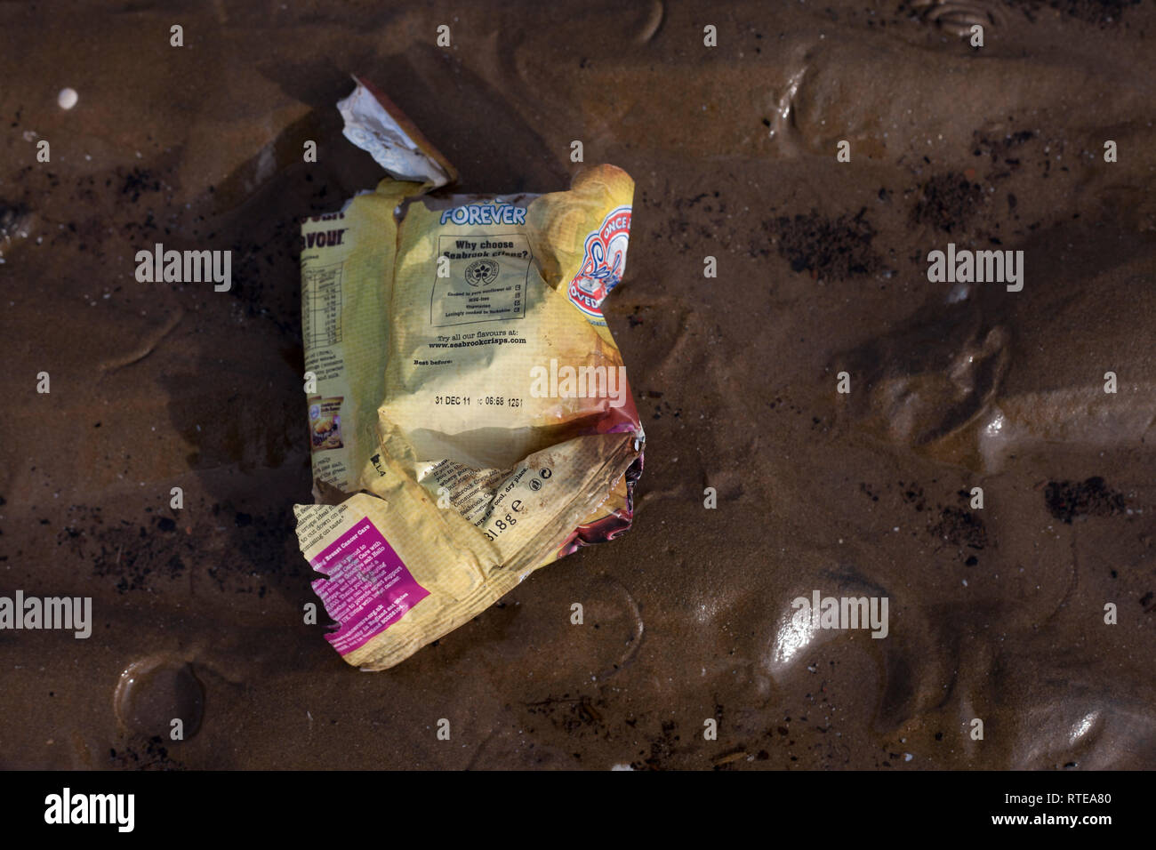Crosby, Merseyside, UK. 1 March 2019. As plastic pollution blights the seas, a crisp bag with a use-by date of 2011 has been washed up on a beach in Crosby, north-west England. Premos/Alamy Live News - Stock Image