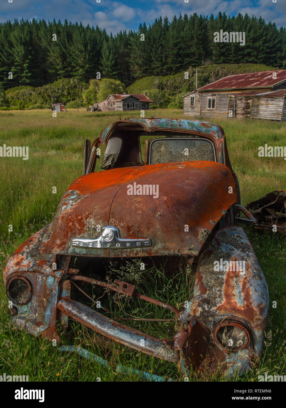 Rusty derelict Bedford truck and abandoned buildings, Endeans Mill, Waimiha, Ongarue, King Country, New Zealand Stock Photo