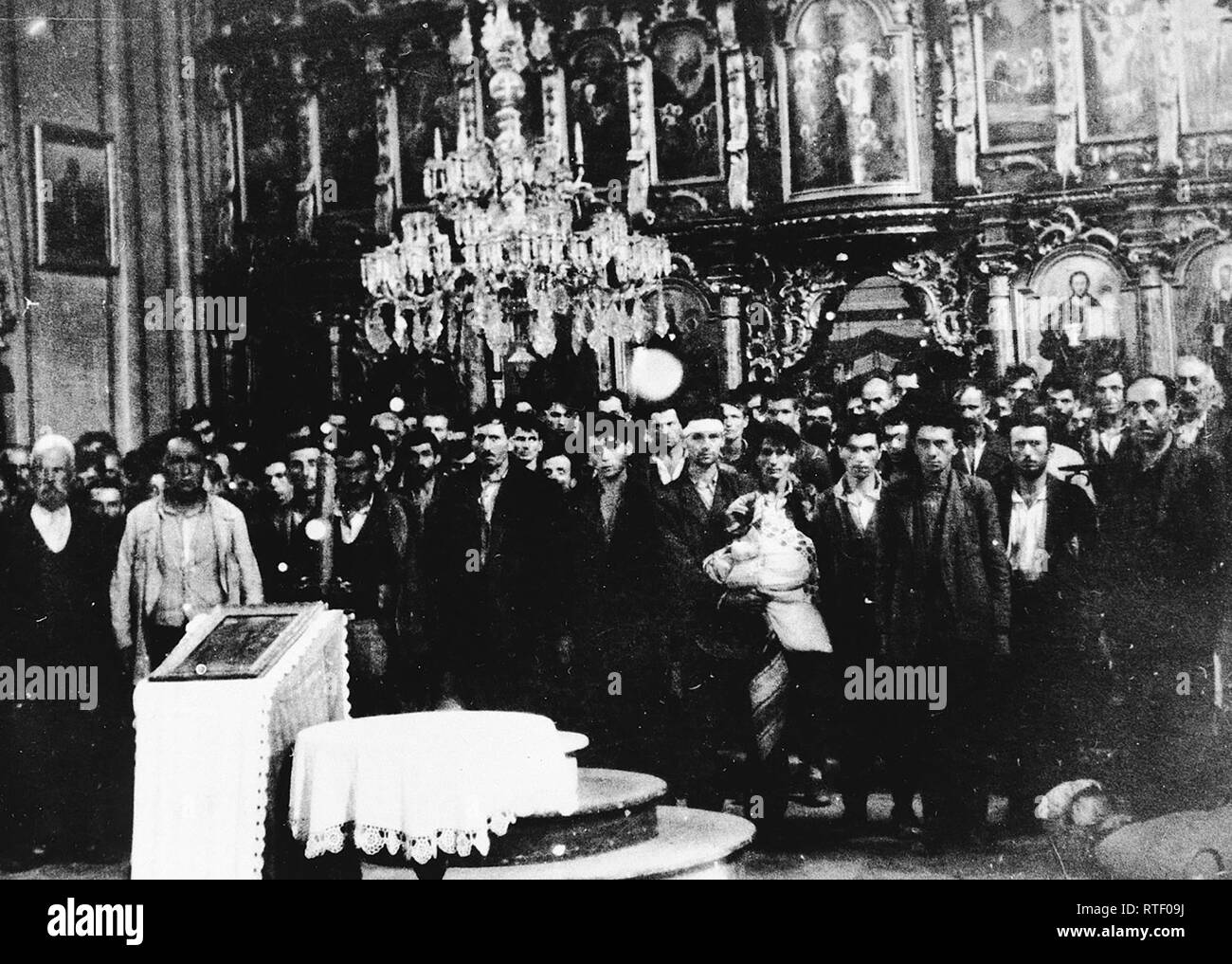 Serbian civilians who are being forced to convert to Catholicism by the Ustasa regime stand in front of a baptismal font in a church in Glina. 30 July 1941 Stock Photo