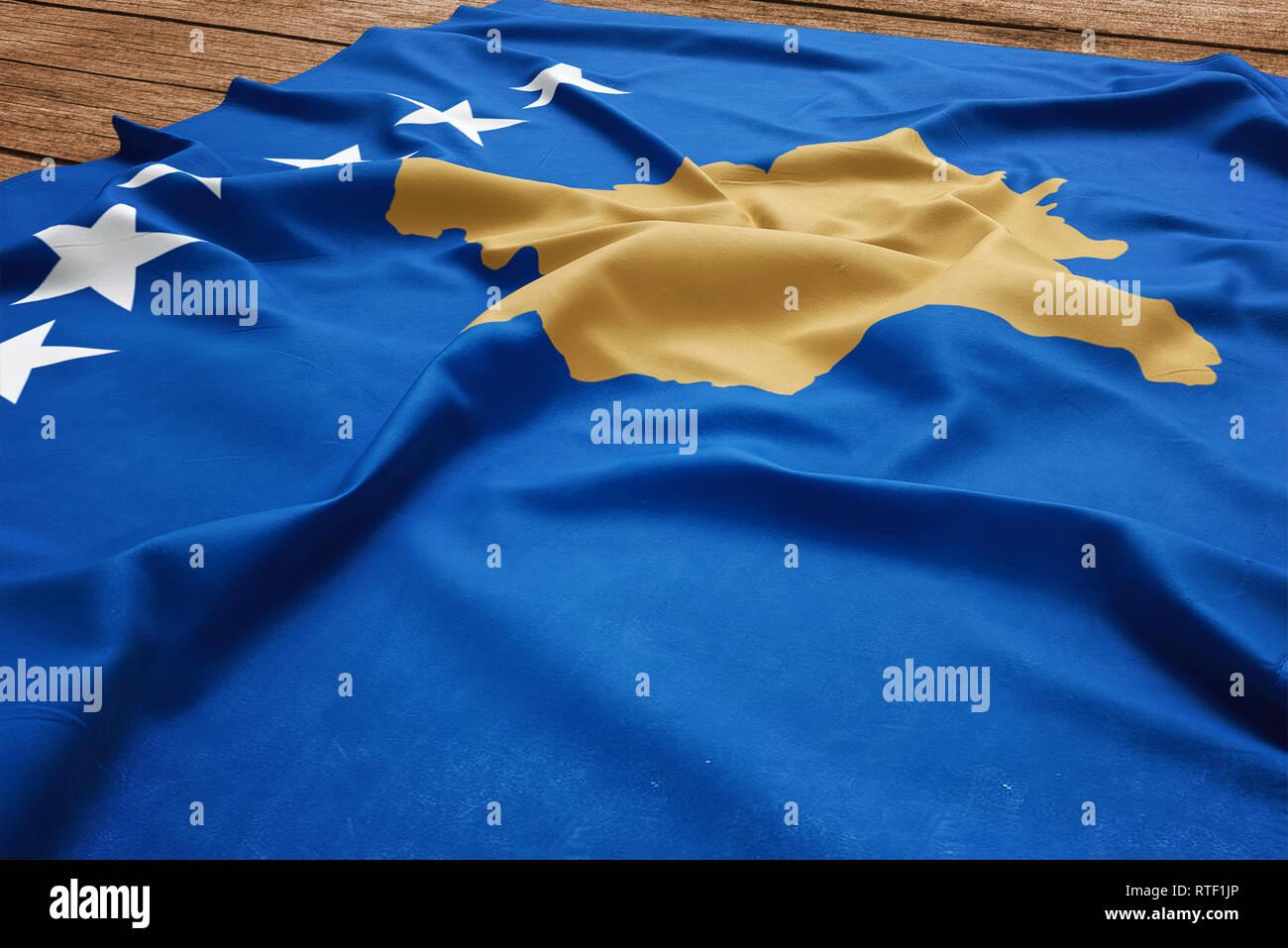 Flag of Kosovo on a wooden desk background. Silk Kosovar flag top view. Stock Photo