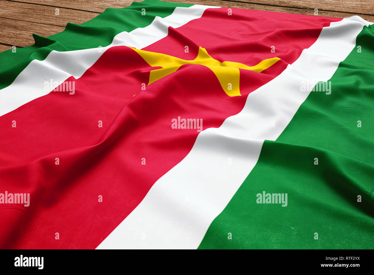 Flag of Suriname on a wooden desk background. Silk Surinamer flag top view. - Stock Image