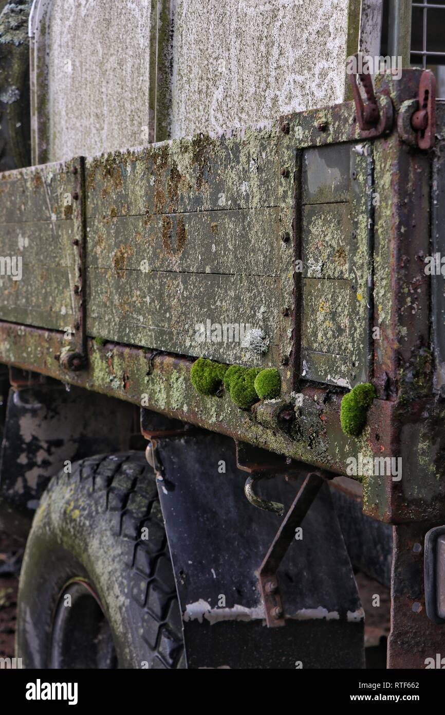 Moss grows on an old agricultural Land Rover with wooden sides, as it slowly decays in a farmers field. - Stock Image