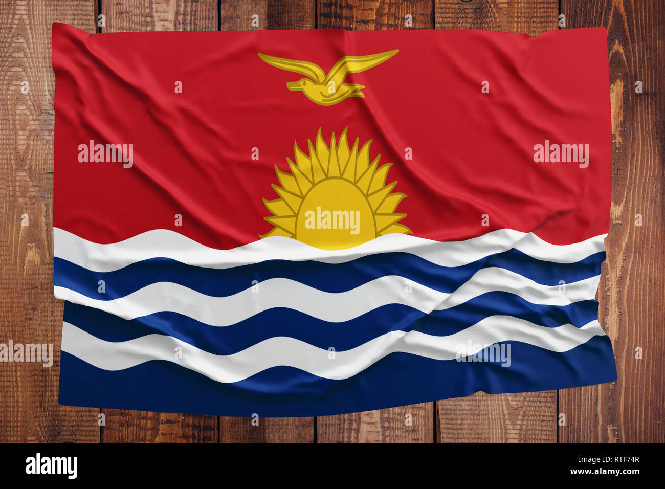 Flag of Kiribati on a wooden table background. Wrinkled flag top view. - Stock Image