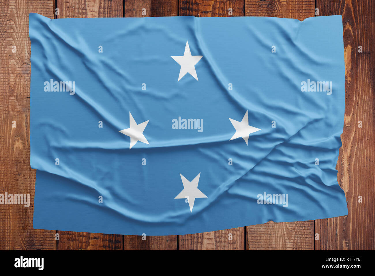 Flag of Micronesia on a wooden table background. Wrinkled Micronesian flag top view. - Stock Image