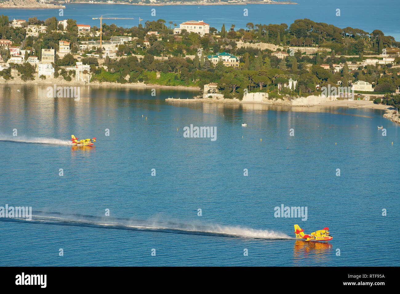 TWO CANADAIR CL-415 REFILLING IN THE SHELTERED BAY OF VILLEFRANCHE-SUR-MER TO COMBAT A NEARBY BRUSHFIRE. Saint-Jean Cap Ferrat, French Riviera, France. - Stock Image