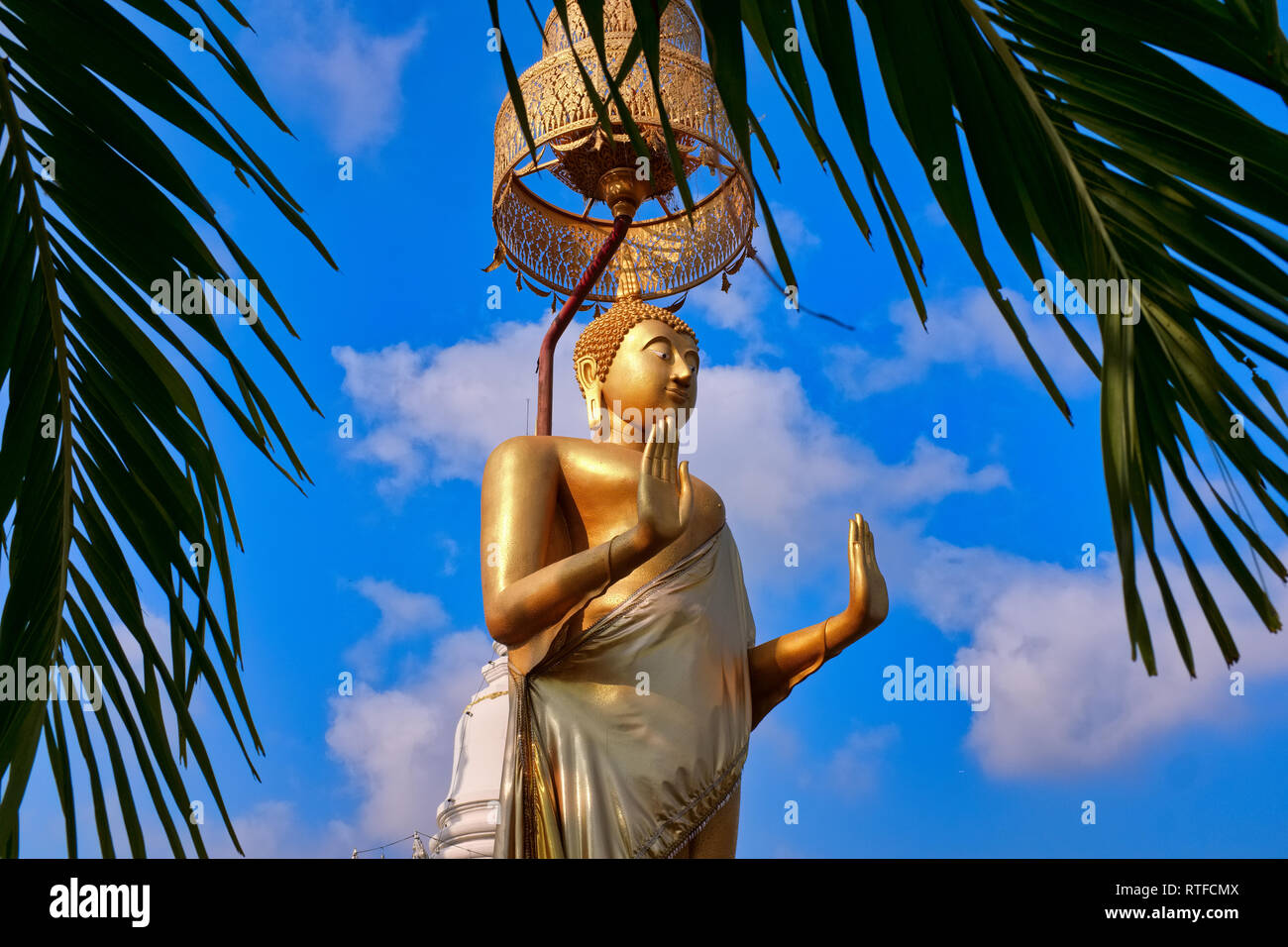 A large standing Buddha in front of Wat Pichaiyat, Thonburi, Bangkok, Thailand, the hands displaying the mudra (posture) of abhaya or fearlessness - Stock Image