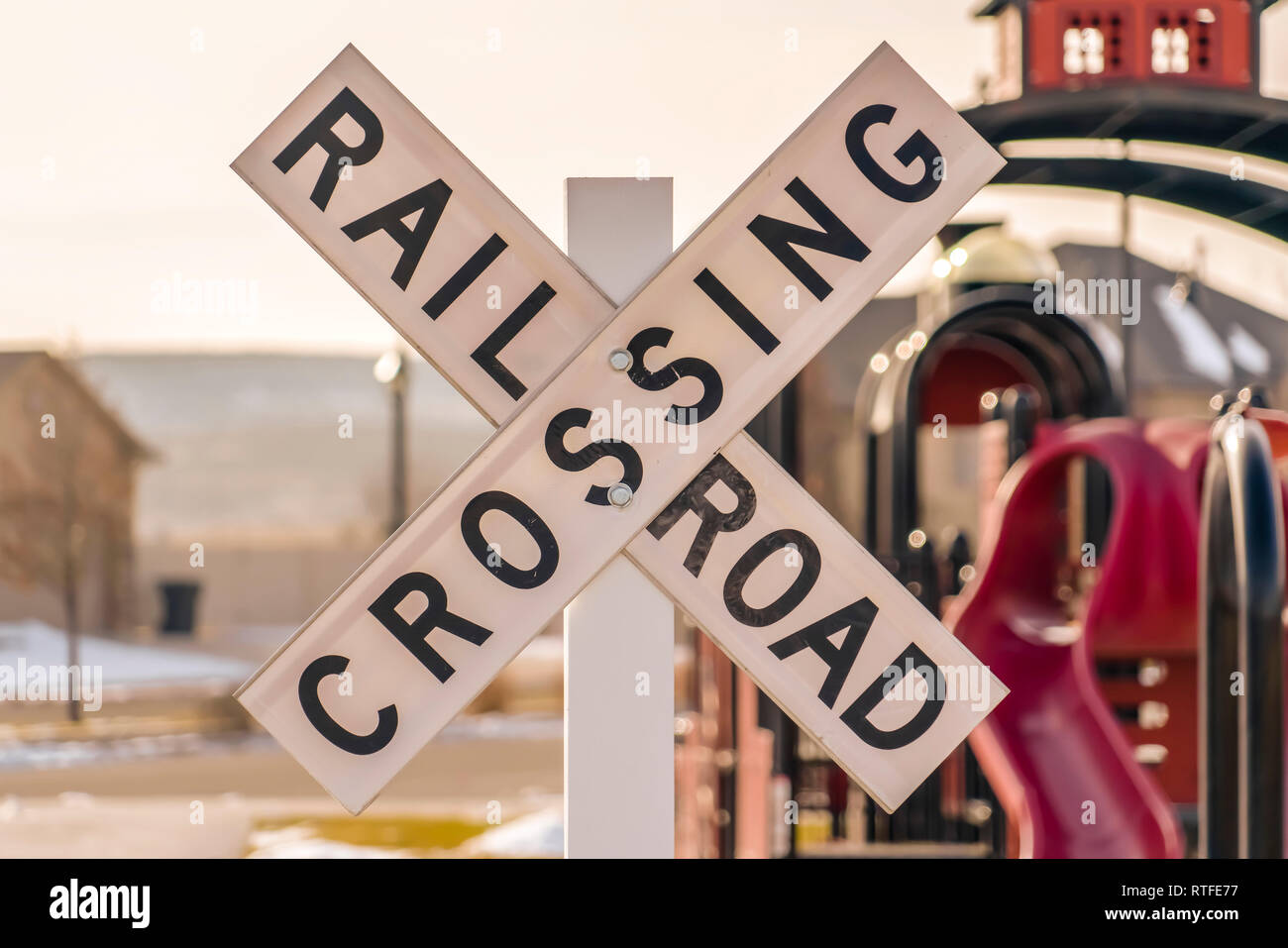 Railroad Crossing sign with playground background  Close up