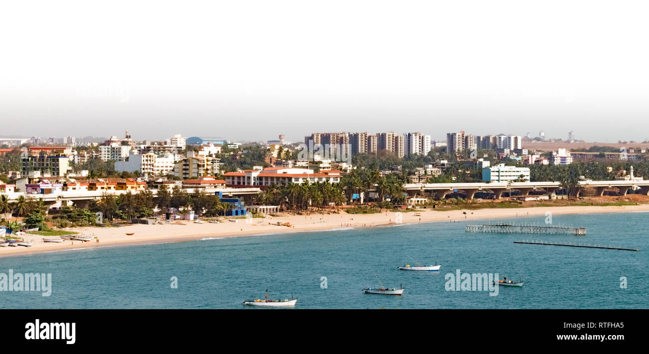 Aerial view of developed city with buildings, beach houses, flyover, palm trees, all situated along the coastline of calm blue sea with anchored boats - Stock Image