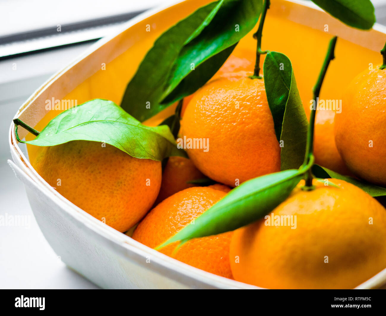 Some oranges with leaves in a basket, Orange Tangerines in a basket on a white background. - Stock Image