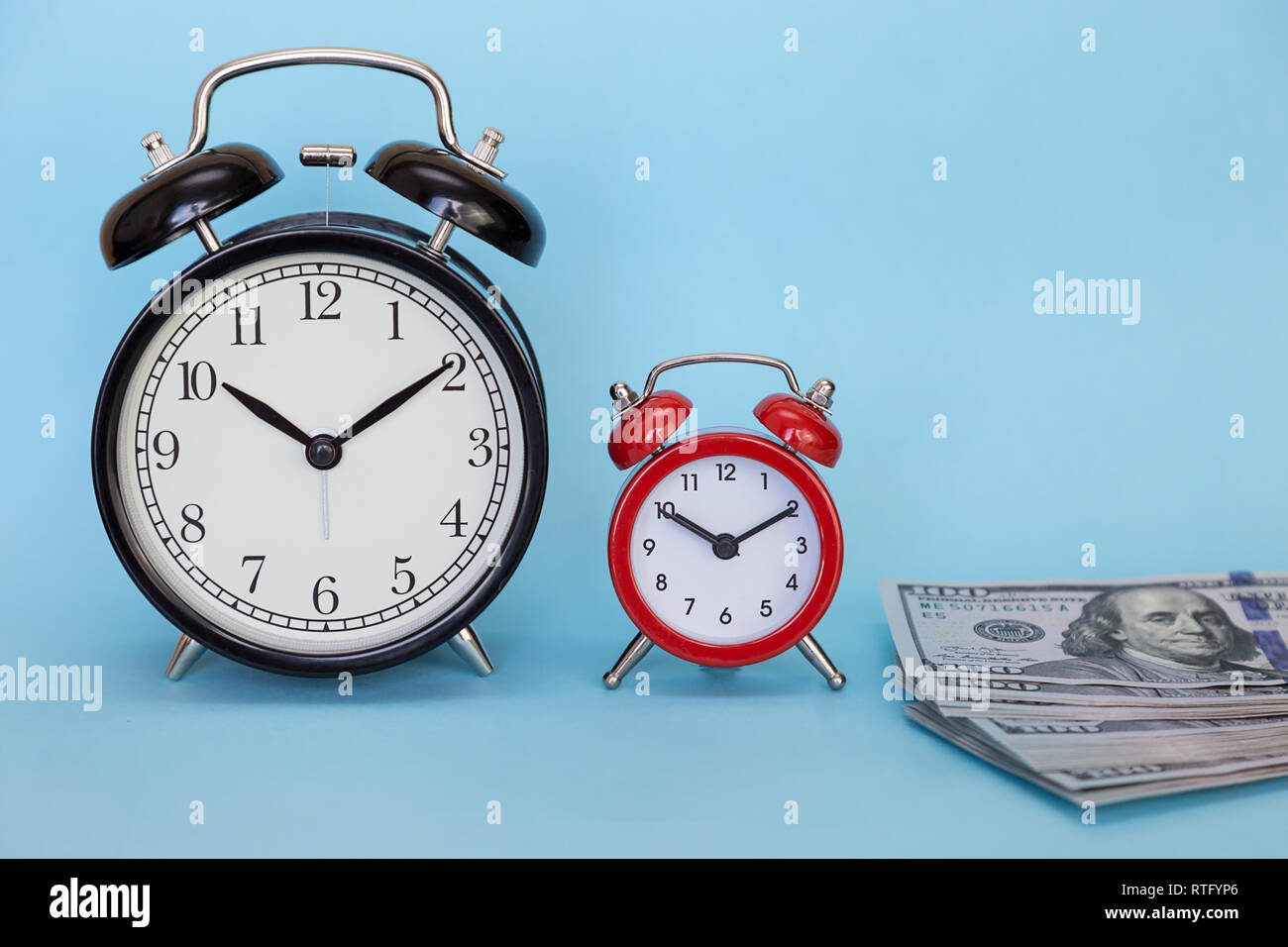 Two retro alarm clock and dollars on a blue background. Concept - time is money Stock Photo