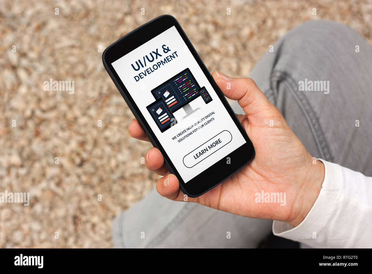 Hand holding smart phone with UI/UX design and development concept on screen. All screen content is designed by me - Stock Image