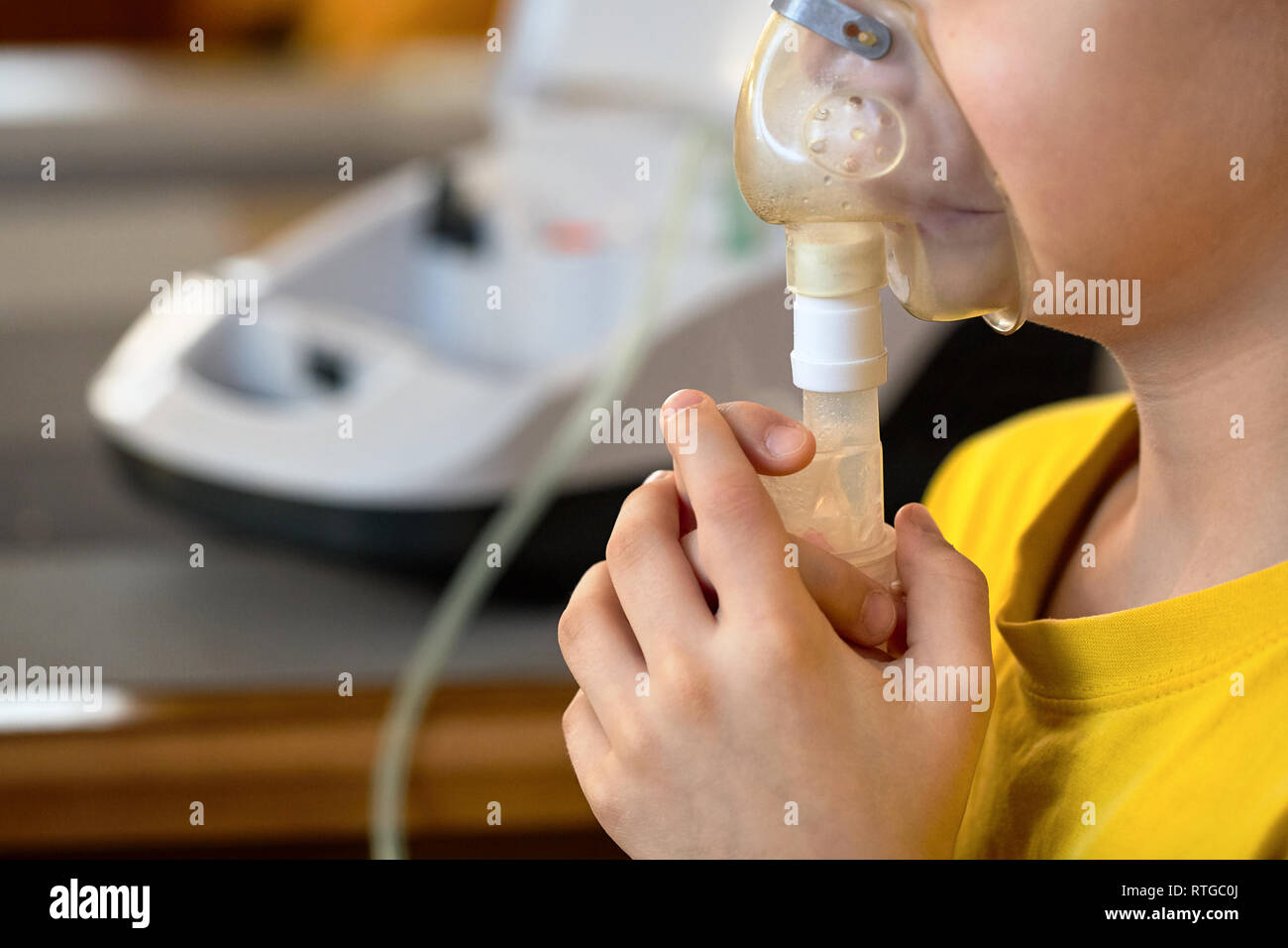 Сhild makes inhalation at home with nebulizer on out of focus background. Example of combating respiratory diseases such as tracheitis bronchitis pneu - Stock Image