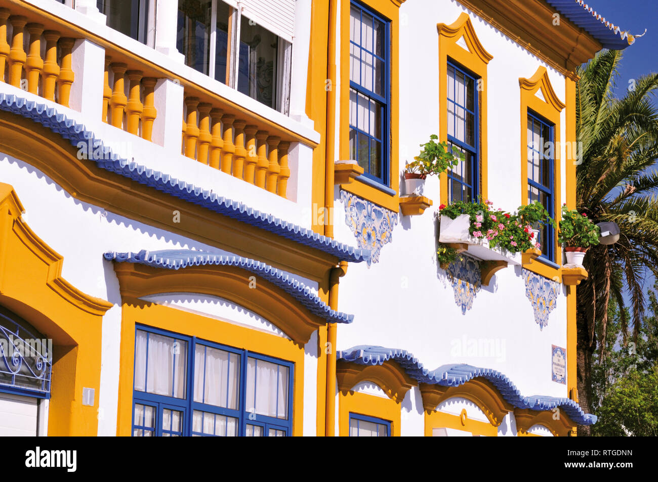 Detail of colorful house facade with yellow and blue windows - Stock Image