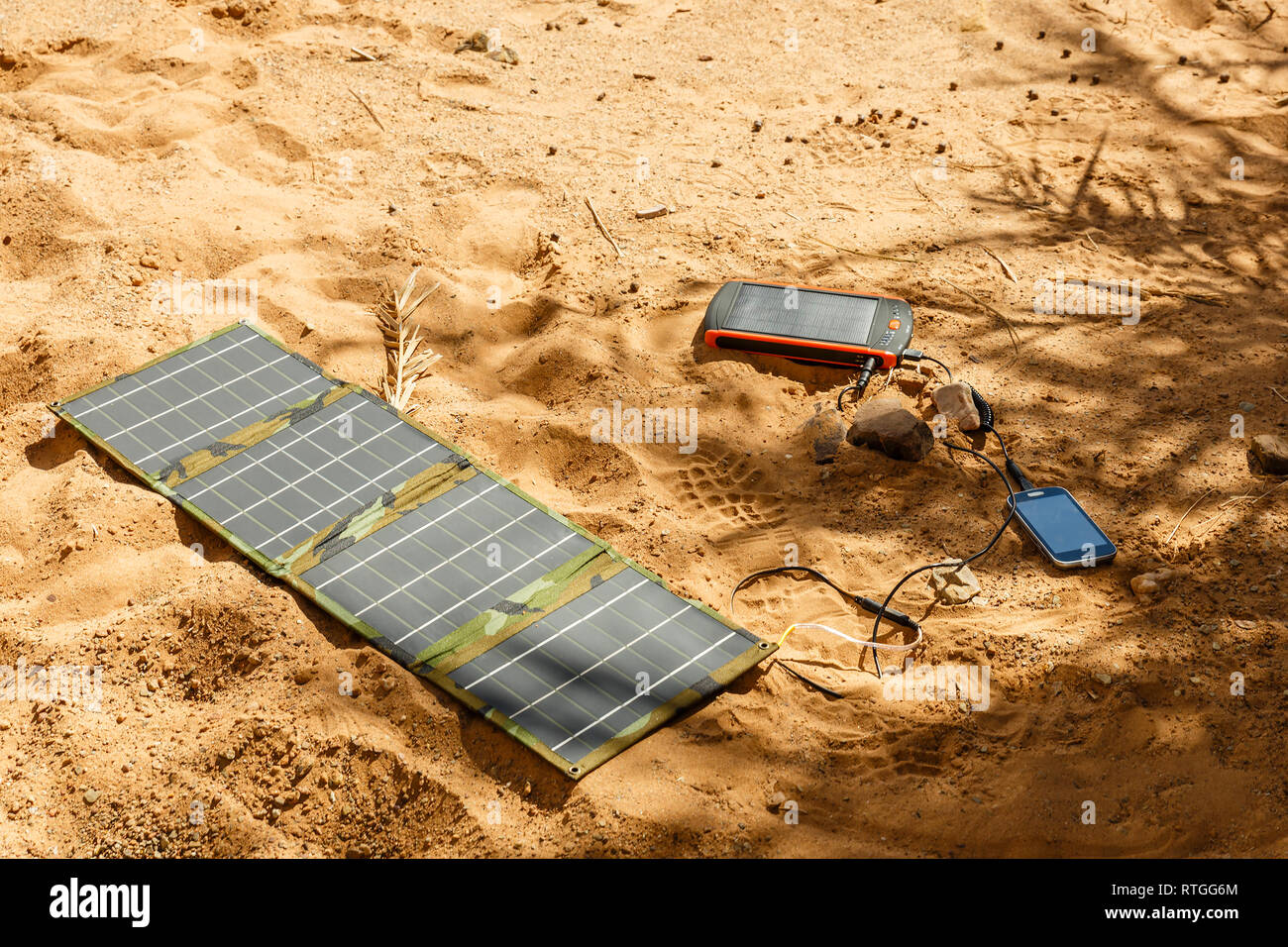 solar panel lying on the ground and charges the smart phone, the Sahara desert. Charge smart phone from the solar battery. - Stock Image