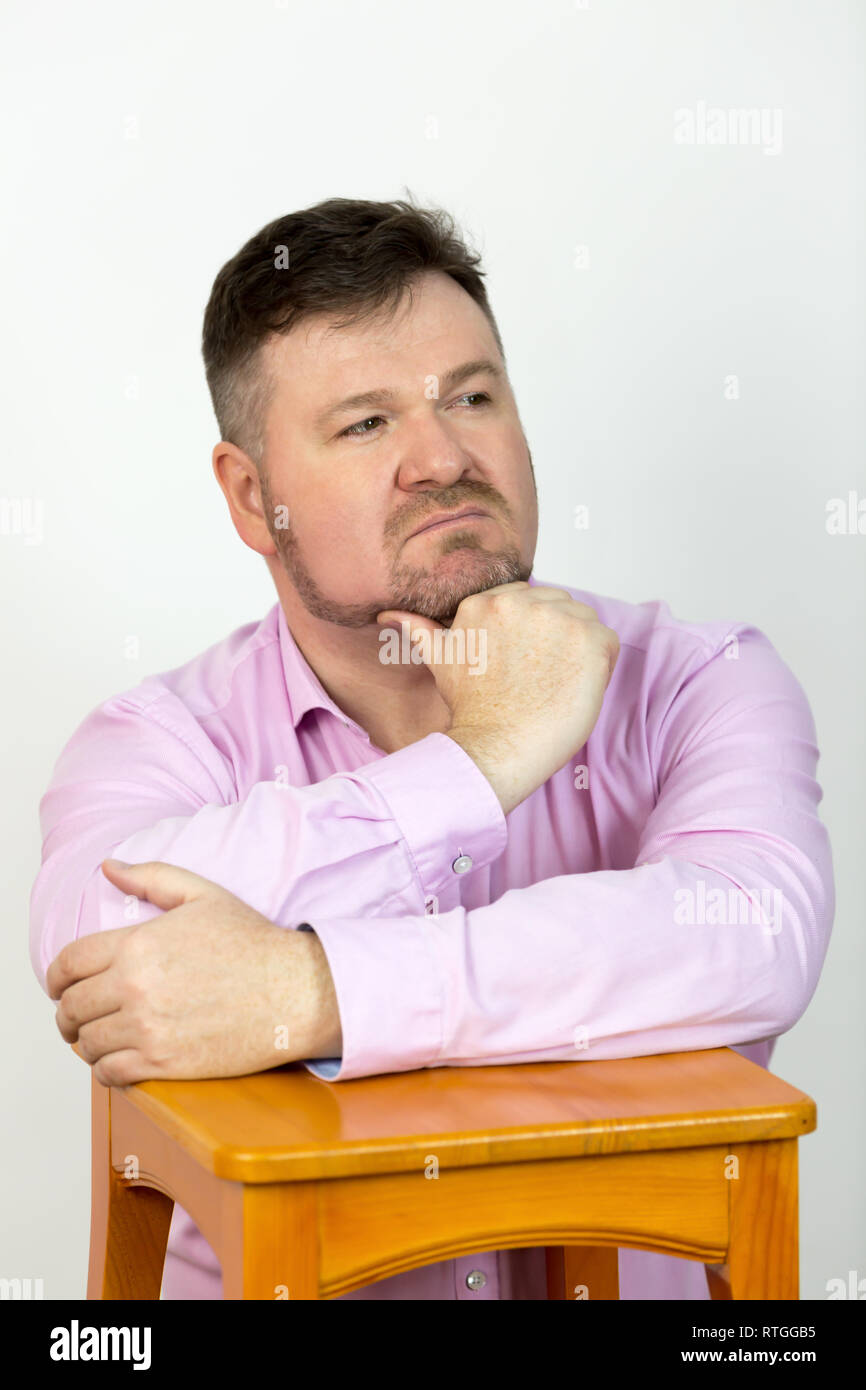 Male 40-45 years old in a pink shirt with a beard on a white background. - Stock Image