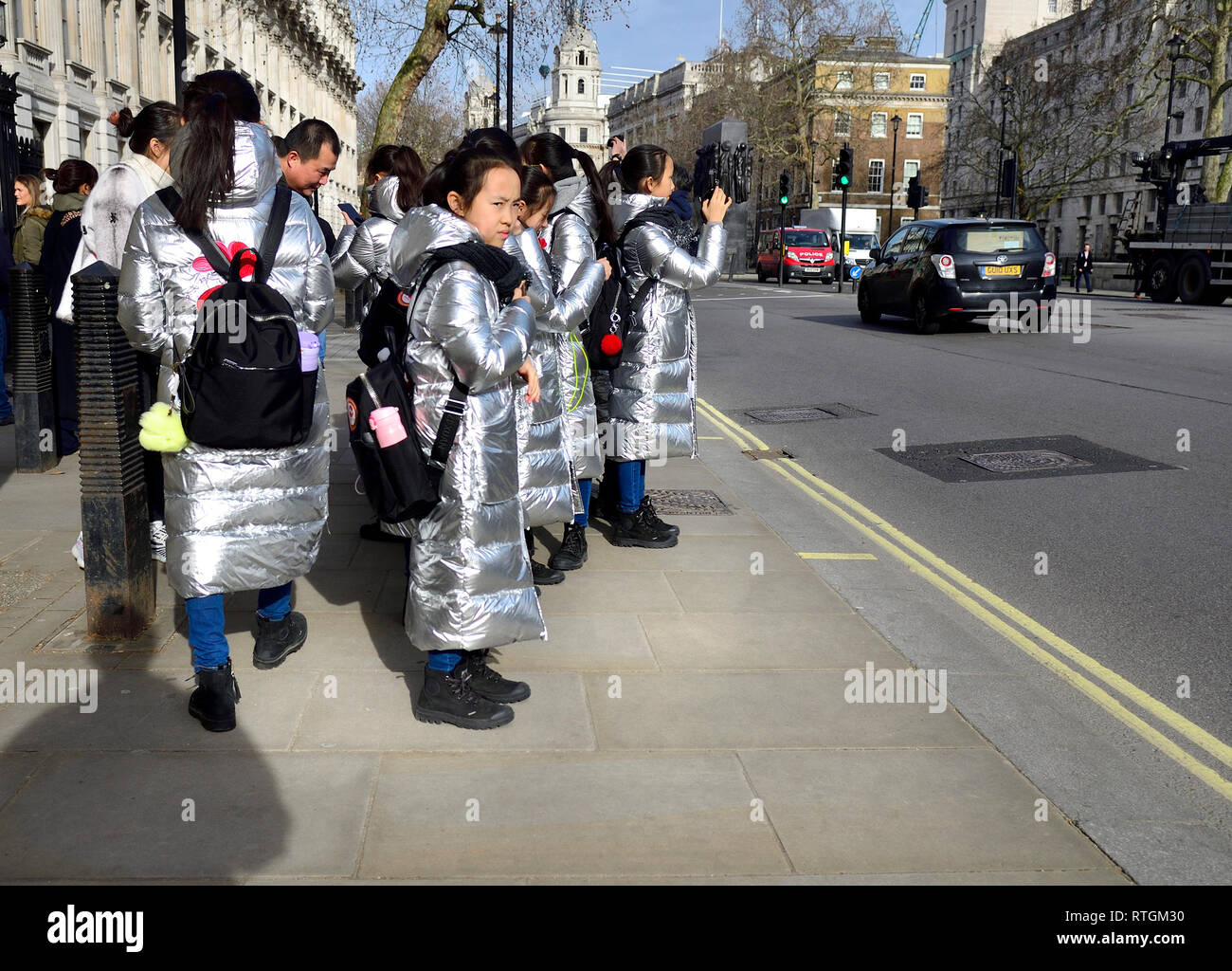 London, England, UK. Group of visiting Japanese schoolchildren in identical silver coats in Whitehall, outside Downing Street - Stock Image