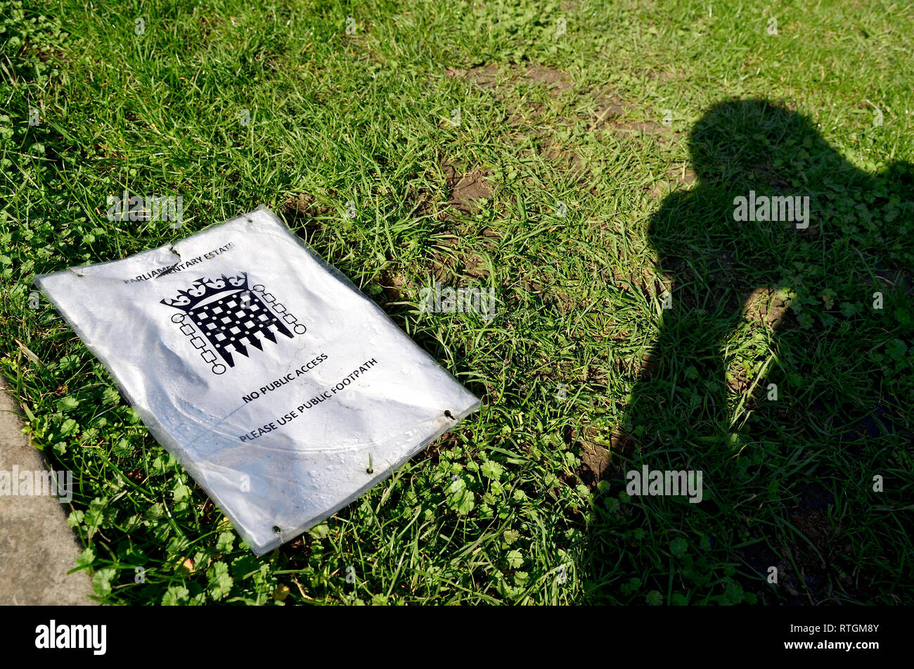 London, England, UK. Discarded sign on College Green, Westminster 'Parliamentary Estate - No Public Access - Please Use Public Footpath' on the grass - Stock Image