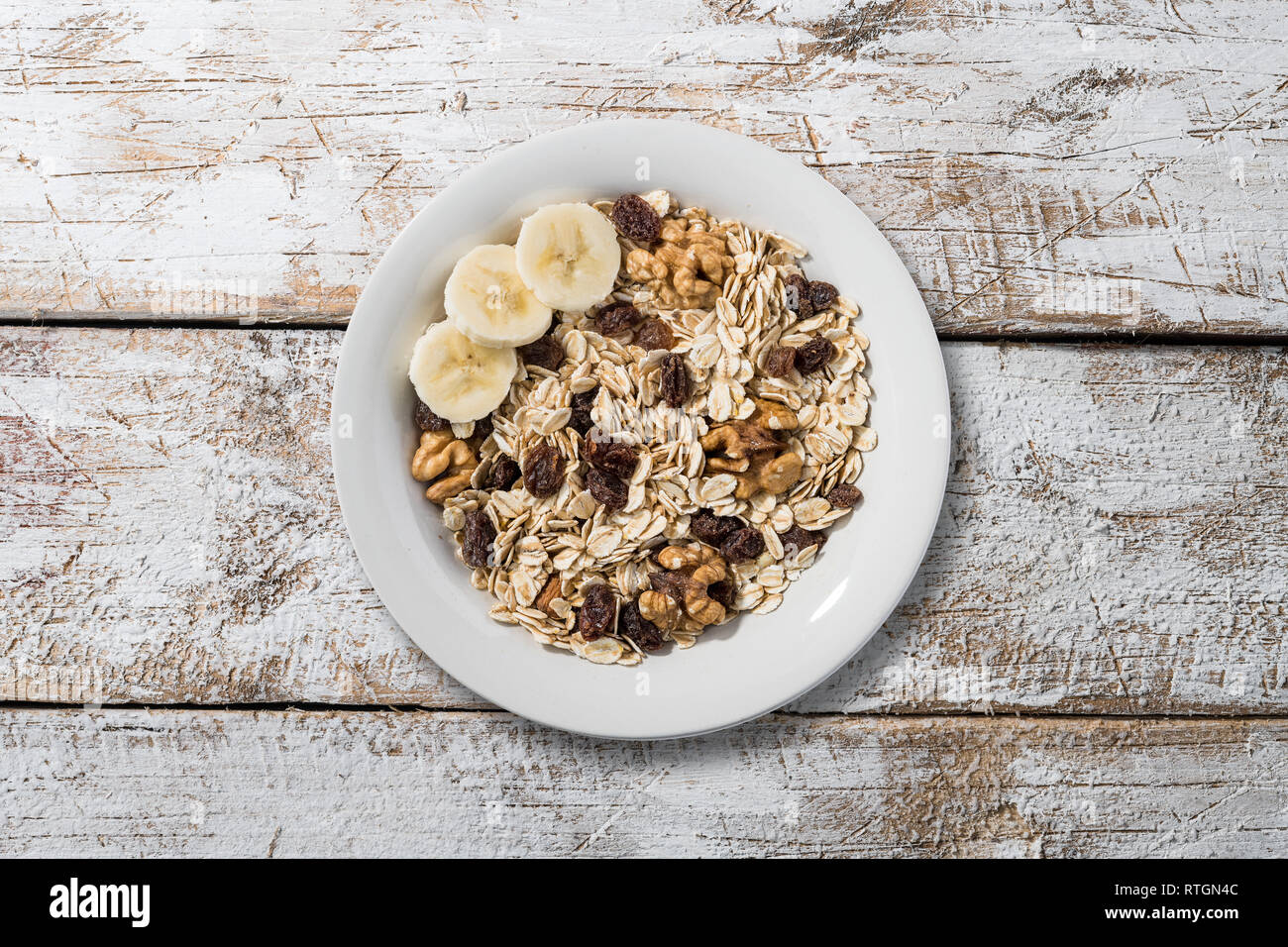 white plate with oat flakes on old wooden table with white colour Stock Photo