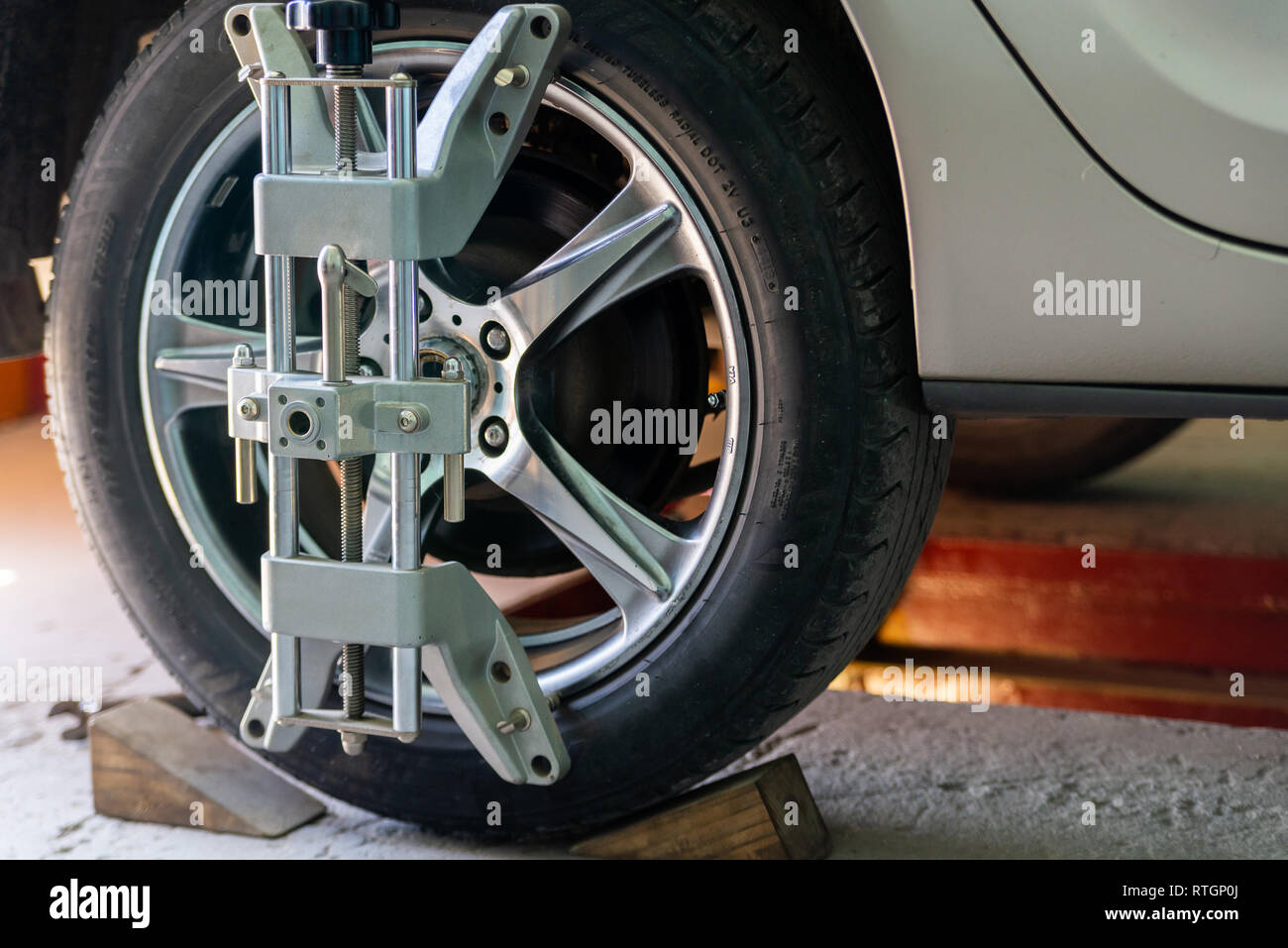 Car on stand with sensors on wheels for wheels alignment camber check in workshop of Service station. - Stock Image