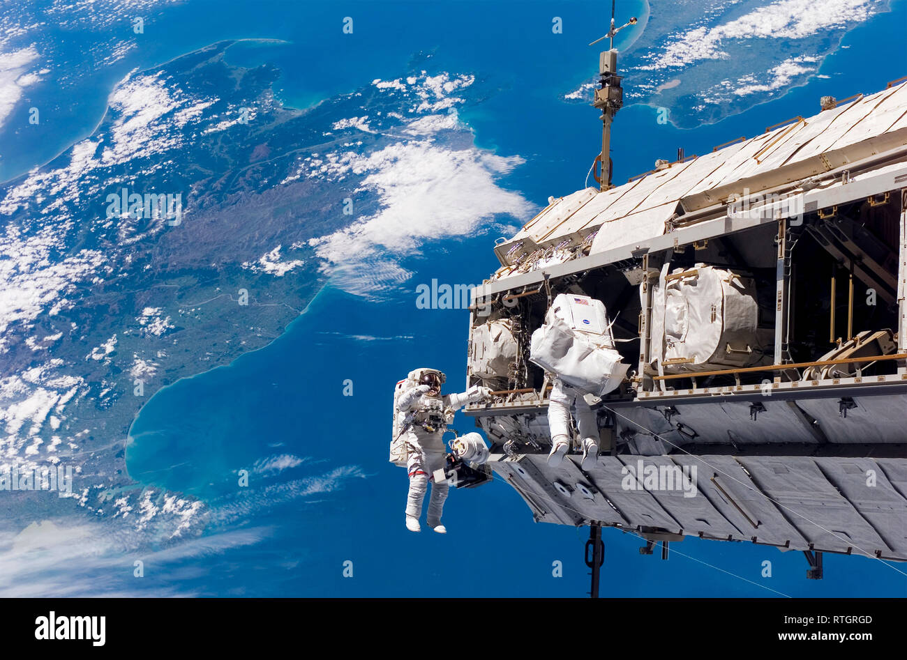 Astronauts and the International Space Station with a view of Earth Stock Photo