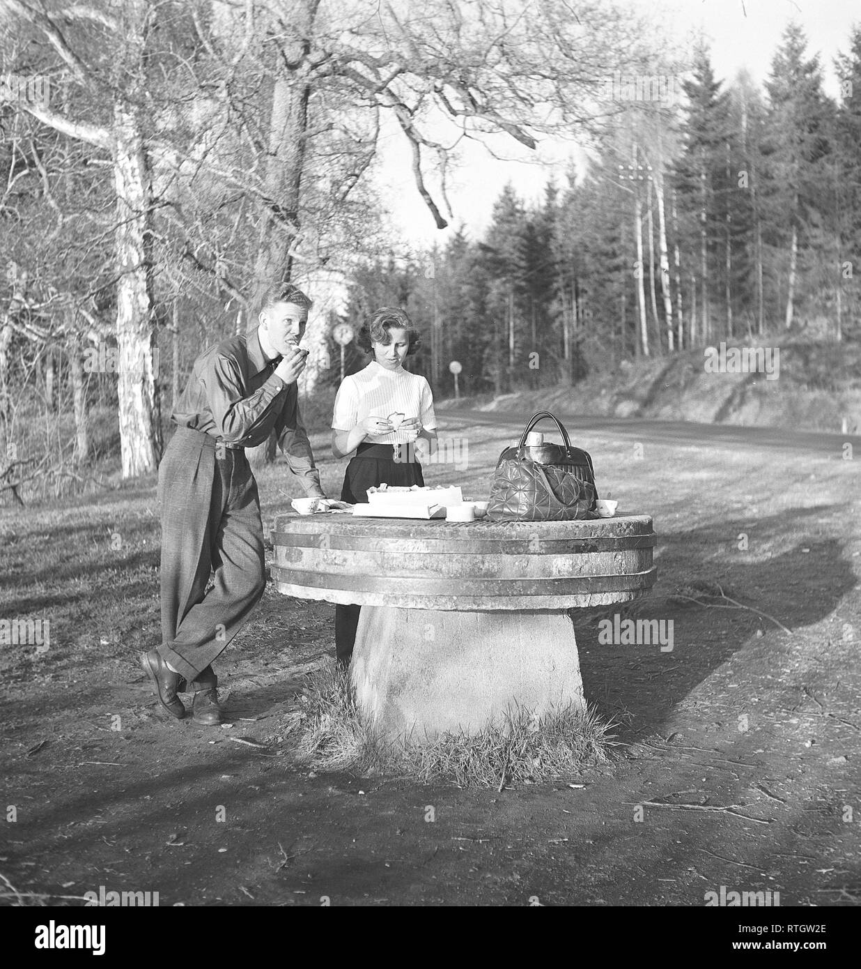 Lifestyle in the 1950s. A young couple has stopped to have a coffee and a sandwich by the roadside. An old millstone makes a good table for the picnic. Photo Kristoffersson Ref BF76-4. Sweden 1952 Stock Photo
