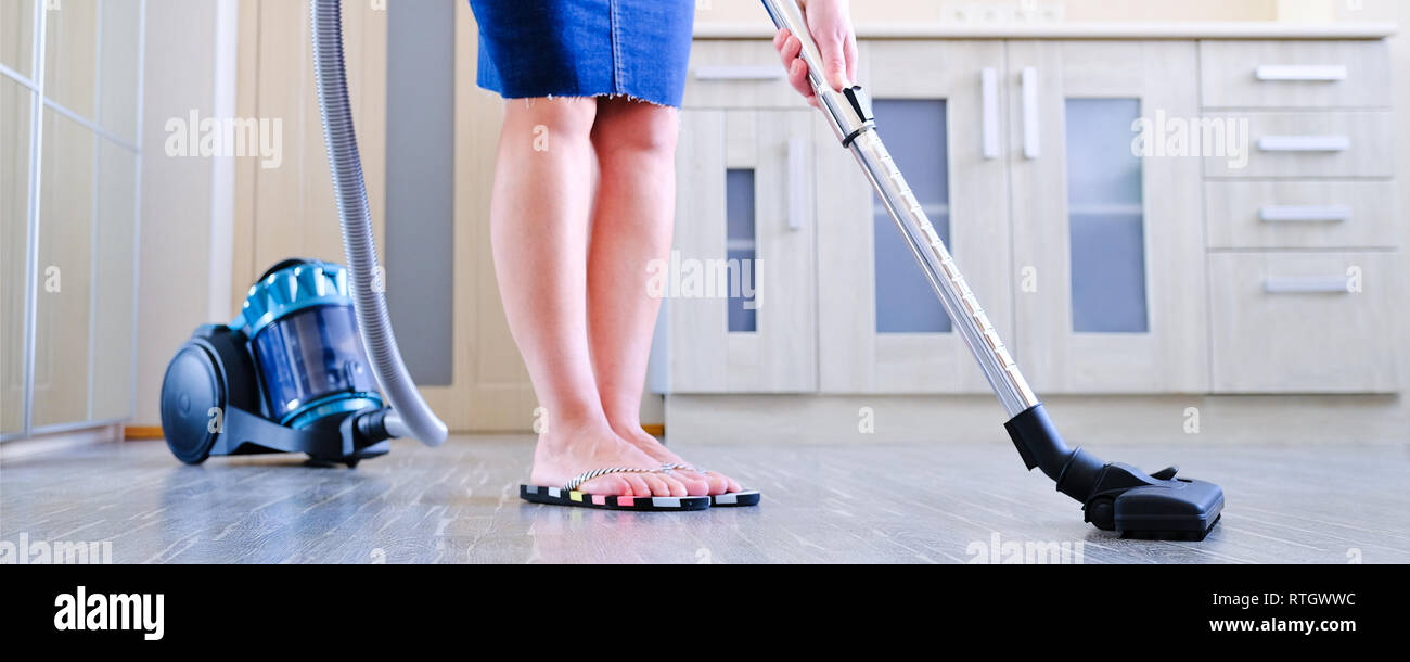 A young woman is cleaning the apartment. In the hands of a household appliance, vacuum cleaner. The concept of cleanliness and order in the premises - Stock Image