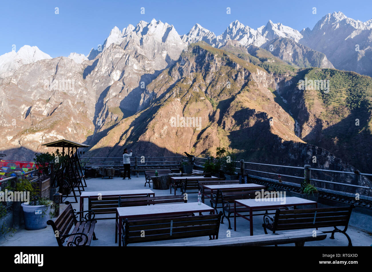 Tourist taking pictures of the mountains from Tea Horse guesthouse's terrace, Tiger Leaping Gorge, Yunnan - Stock Image